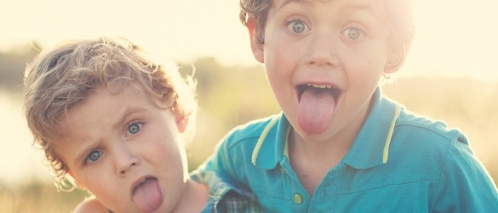 Two male toddlers sticking out their tongues